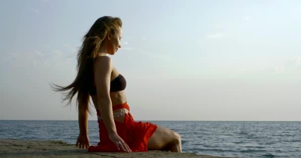 sexy žena sedí na betonových nábřeží na mořské pobřeží ve dne