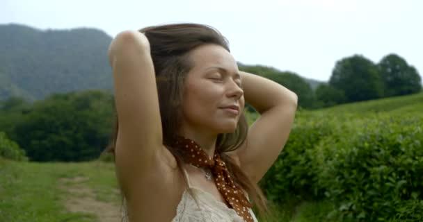 entspannte und glückliche Frau genießt gutes Wetter und atmet Bergluft auf Teeplantagen