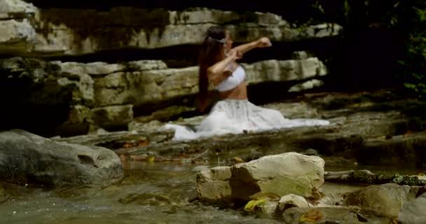 Waldwasserquelle ergießt sich über Steine und schöne indische Mädchen sitzt und tanzt im Hintergrund