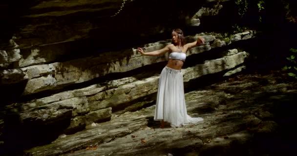 charmante Dame tanzt orientalischen Tanz im Wald, der in der Nähe von Felsen steht