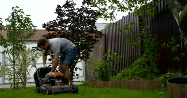 man takes off container from lawn mower in garden slow