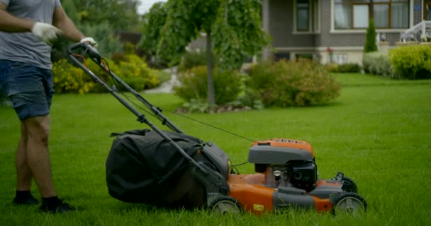 man in grey t-shirt starts lawn mower on grass slow motion