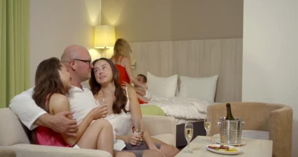 Swinger-Party von fünf Personen im Schlafzimmer, Paar haben Sex auf dem Bett, Mann flirtet mit zwei Frauen