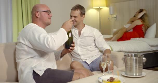 zwei Lesben streicheln auf dem Bett und ihre Ehemänner öffnen Champagner im Vordergrund
