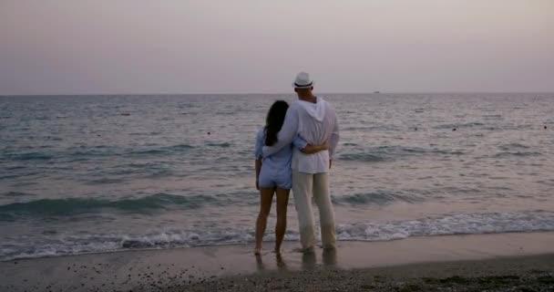 szerető házastársak ölelni, és csodáló tengeri horizont Alkonyat idején, állva a strandon