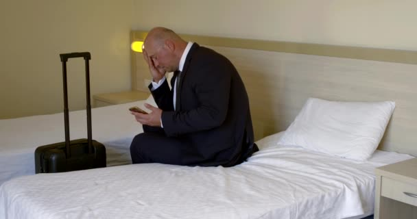 A bald businessman in a business suit sits on a bed in a hotel room, a travel bag is by the bed, he sadly looks at the phone and rubs his face and forehead.