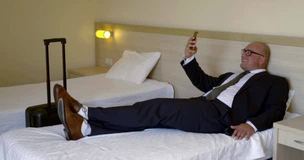 Bald businessman in glasses, business suit and shoes lying on the bed in a hotel room, the bed is a travel bag, he takes a selfie on a smartphone, smiling.