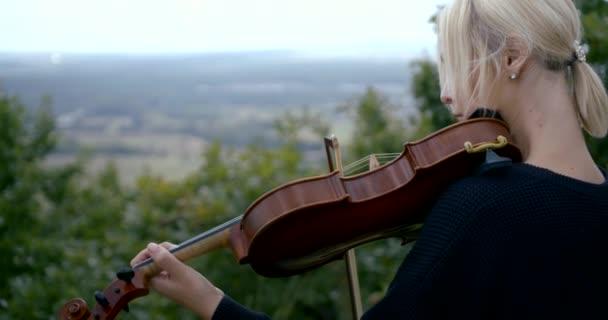 szőke nő játszik hegedű szabadban nyári napon, közepes shot