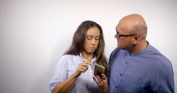 Adult married couple, enjoy smartphone on white background. A bald man in glasses and his charming wife look at information on the Internet and discuss