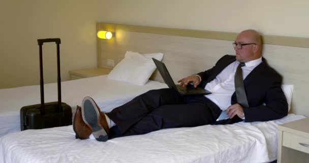 serious businessman in glasses types on laptop in hotel