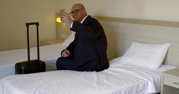 usmívající se muž v obleku dělá fotku hotelového pokoje na posteli
