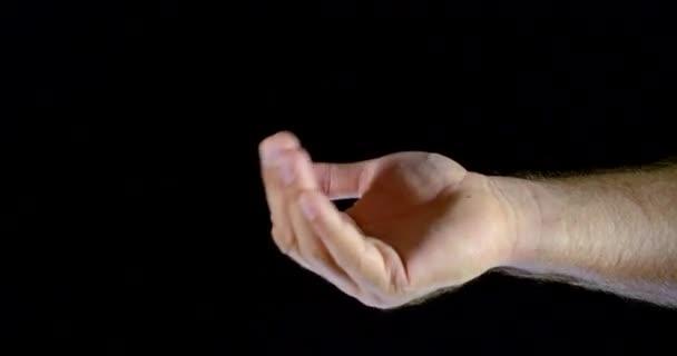 Blízký pohyb mužské ruky s dlaní a prsty na černém izolovaném pozadí