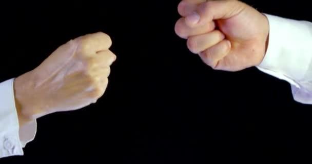 Nahaufnahme männlicher und weiblicher Hände in weißen Hemden, die auf schwarzem Hintergrund eine Steinpapierschere spielen
