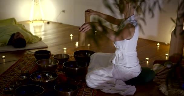 tibetische Praxis: das Mädchen führt eine Sitzung der Klangtherapie durch, Massage mit Klangschwingungen mittels Schalen, Kerzen um sie herum liegen entspannte Menschen.