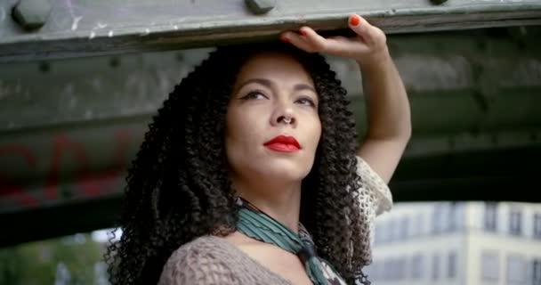 Nahaufnahme Porträt eines strahlend schönen brünetten Mädchens mit lockigem Haar, ihren roten Lippen und einem Nasenpiercing. Sie steht unter der Brücke und posiert mit einem Taschentuch um den Hals.