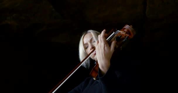 Portré egy szőke nő, aki játszik a hegedű, ez egy fekete háttér.