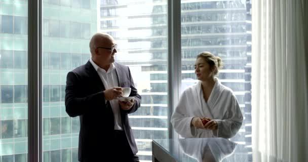 Ein Geschäftsmann im Businessanzug trinkt seinen Morgenkaffee mit seiner Frau am Küchenfenster. seine Hausfrau trägt einen weißen Mantel und isst einen Apfel