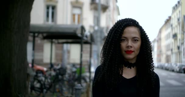 wunderbare Brünette mit lockigem Haar steht auf der Straße der Stadt