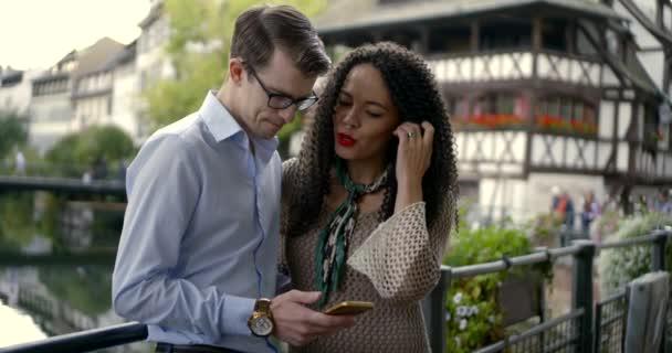 Paar steht am Brückengeländer und tippt auf Smartphone