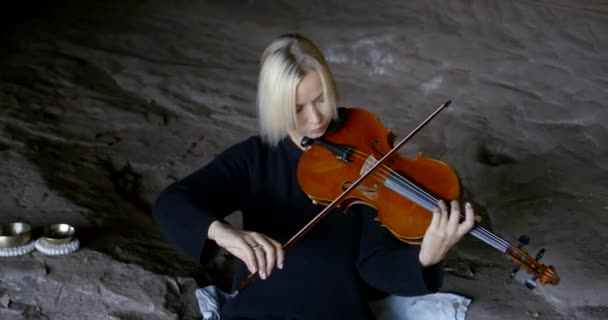 young woman plays brown violin sitting in large cave