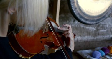 Close-up portrait of a blonde woman sitting on a stone surface and conducts sound therapy, massage sound vibrations, playing the violin, standing around her tambourines.