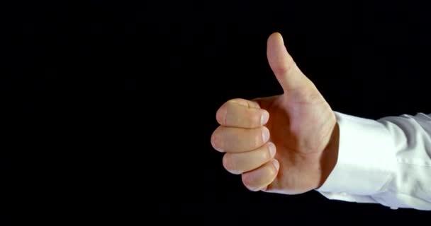 Közeli fel egy Mans kéz egy fehér hüvely egy fekete háttér a stúdióban, ő gesztusok, először bemutatja a szuper jel-remek, majd bemutatja az OK Sign.