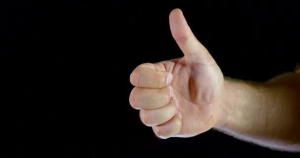 Zblízka v bílém rukávu na černém pozadí ve studiu je vidět nápis super-palce nahoru.