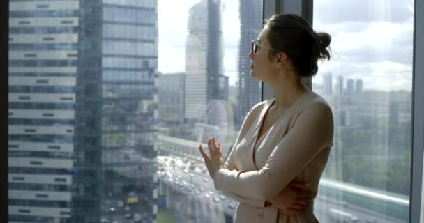 portré egy sötét hajú üzletasszonyról szemüveggel és piros rúzzsal, aki az üzleti központban áll egy nagy panoráma ablaknál, mögötte felhőkarcolók.