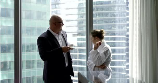 nő a köntösben beszél a férjével üzleti öltönyben, kávét iszik lakásban