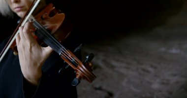 professional musician plays brown wooden violin in darkness