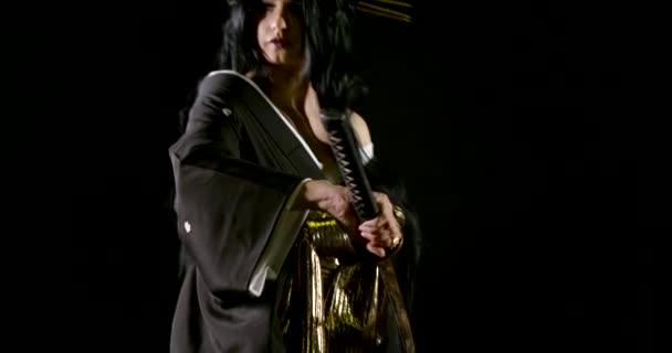 Kriegerin Samurai in einem Kimono, trägt ein uraltes Katana-Schwert aus der Scheide auf schwarzem Hintergrund