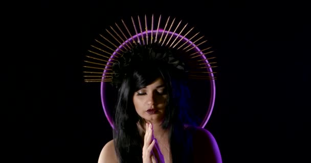 brunette woman is standing in front of violet neon lamp, folding palm, wearing golden spiked crown