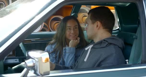 eine dunkelhaarige Frau in Jeansjacke sitzt in einem amerikanischen Oldtimer, ein Mann sitzt neben ihr am Steuer, sie reden, die Frau lächelt und lehnt sich an ihre Hand, hört dem Mann zu, schaut ihn an.