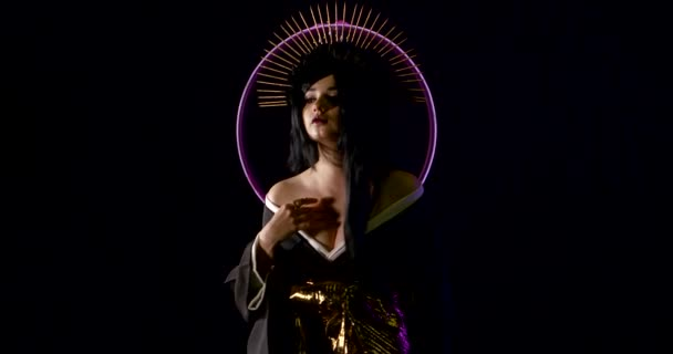 sexual woman dressed in kimono and golden spikes halo crown is standing in dark studio