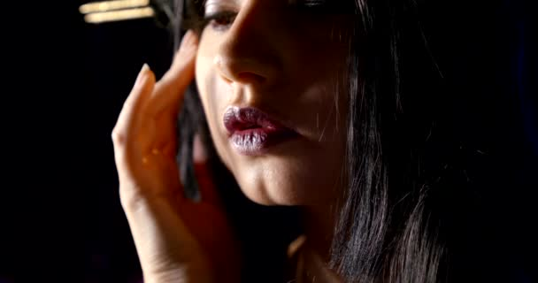 beautiful brunette girl with fashion makeup is touching her face by fingers, closeup view in darkness