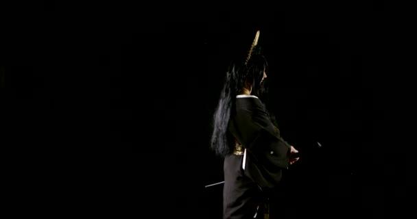 junge brünette Frau nimmt Schwert von Scheide und greift Feinde in der Dunkelheit an