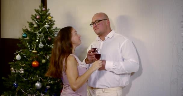Erwachsene glückliche Menschen, die sich mit Sektgläsern auf dem Hintergrund eines geschmückten Weihnachtsbaums küssen. ein verliebtes Paar feiert Weihnachten oder Neujahr und trinkt Champagner
