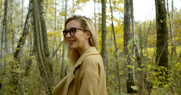 junge Frau mit Zahnspange und Brille im Gesicht steht an einem Herbsttag im Wald, lächelt und dreht sich
