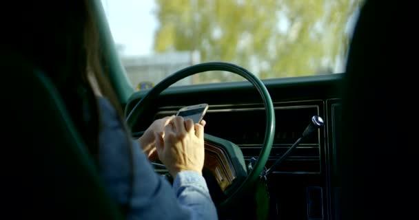 Nahaufnahme einer dunkelhaarigen Frau, die am Steuer eines amerikanischen Oldtimers sitzt und in ein Mobiltelefon schaut. Rückansicht.