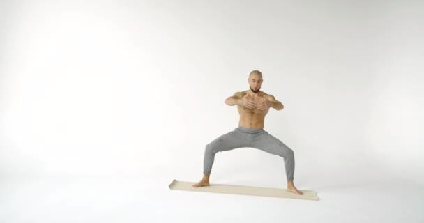 athletischer Mann spannt Muskeln seines Körpers an, macht Kniebeuge in statischer Position im Studio
