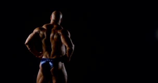 Tělo brutální plešatý svalnatý muž kulturista detailní up na černém pozadí, pózuje, ukazuje svaly. Pohled zezadu..