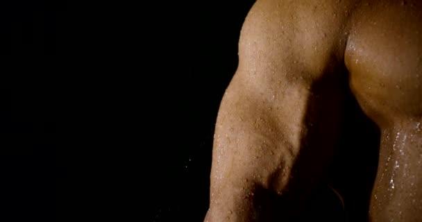sexuell muskulös nackter Körper eines starken Mannes, der in der Dunkelheit unter der Dusche steht, Nahaufnahme