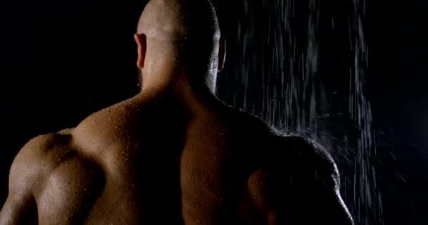 nagy izom sportoló áll zuhany alatt víz patak, visszapillantás sötétben