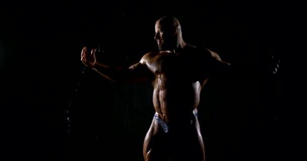 männlicher nackter Jock steht in der Dunkelheit unter Wasser und demonstriert seine Muskeln