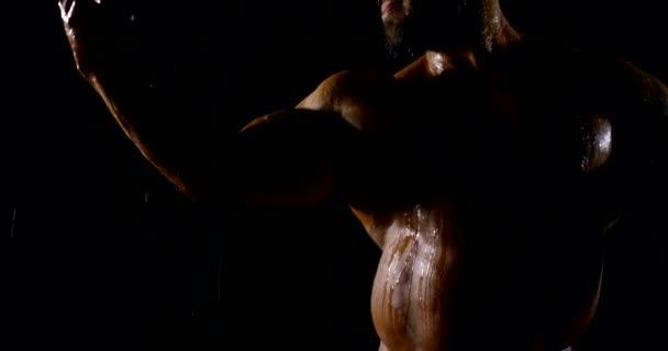 plešatý vousatý sportovec s tvrdými svaly stojí pod vodou teče v tmavém studiu