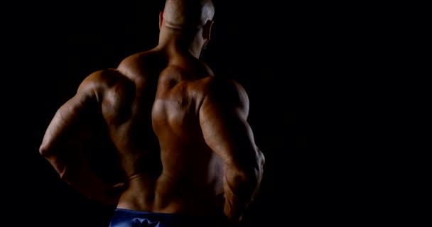 starker halbnackter Mann steht mit dem Rücken zur Kamera und zeigt seine Muskeln im dunklen Raum
