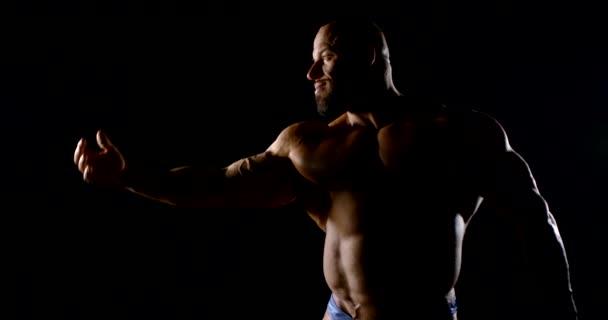 bulliger Mann mit nacktem Oberkörper steht im Dunkeln und beugt die Hand, um Muskeln zu demonstrieren