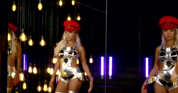 confident blonde woman is dancing and walking in hall of nightclub, looking at camera