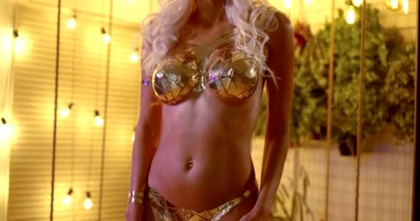 sexuell nackte blonde Frau posiert für die Kamera, ihre Brust ist mit golden glänzendem Metallband bedeckt
