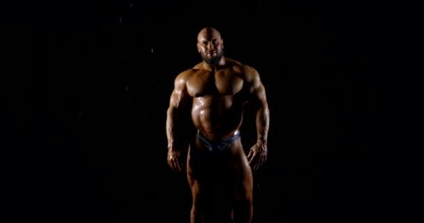 Ein muskulöser, glatzköpfiger Bodybuilder mit Bart tritt unter den Wasserstrahlen in die Kamera. dunkler Schlüssel